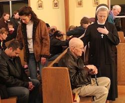 Laicos y religiosas imponen manos orando por sus hermanos
