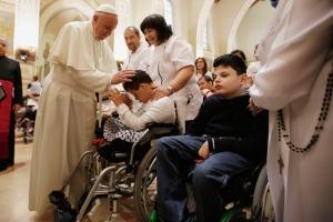El Papa Francisco imponiendo las manos a un joven impedido