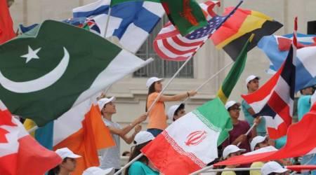 Jóvenes agitan banderas de diversos países en la Plaza de San Pedro.